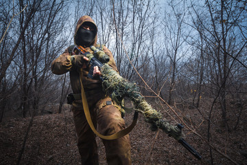 Sniper wearing camouflage suit with rifle walk in the woods