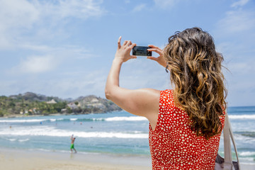 Mixed race woman taking pictures of tropical beach