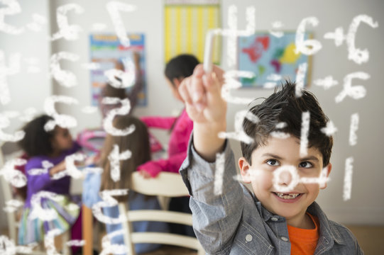 Boy doing math problems in classroom