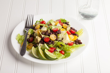 Southwest black bean, lime, cilantro, tomato, and avocado salad on a vintage antique plate with water
