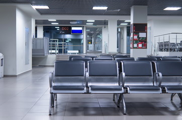 Waiting zone in an airport with grey chairs.