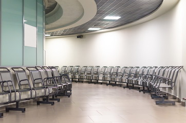 departure lounge in an airport with chairs. Round galary.