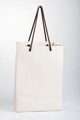 Old paper bag with rope handles on a white background