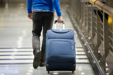 Traveler pulling suitcase close-up