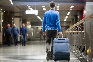 Traveler pulling suitcase at airport