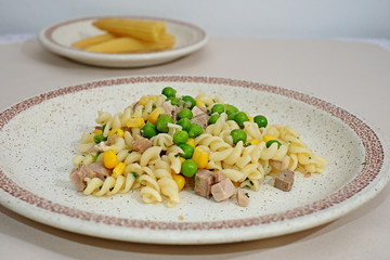 Homemade pasta with green peas corn and meat