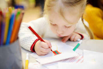 Cute preschooler girl drawing a picture