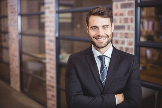 Handsome businessman with arms crossed standing in office