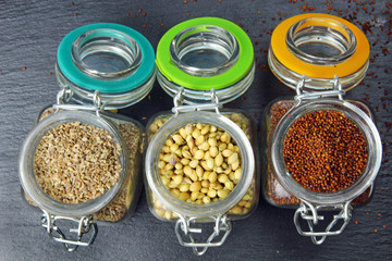 Aromatic spices of coriander seeds, mustard seeds and carom seeds in glass jars on a grey background.