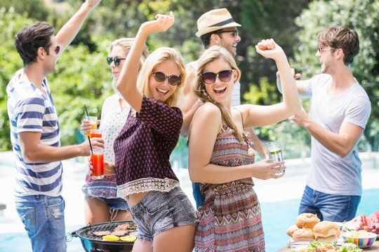 Group of friends dancing at outdoors barbecue party