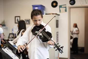 Caucasian boy playing violin in music class