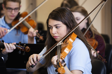Students playing violin in music class