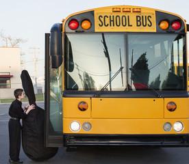 Caucasian boy carrying bass onto school bus