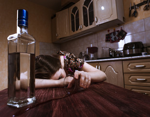 Sleeping drunk woman with inverted glass in hand