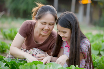 Happy Asian daughter gardening with her mother