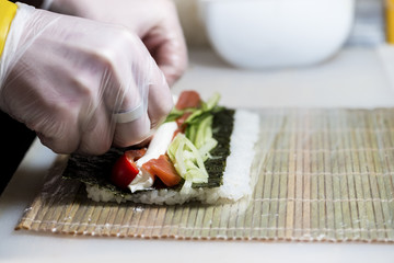 closeup of chef preparing sushi in the kitchen, shallow DOF