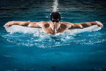 Muscular young man swims the butterfly