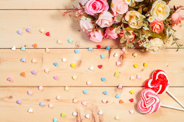 Pastel color tone  roses flowers with heart shape candy on woode