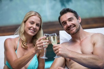 Couple sitting on sun lounger toasting champagne