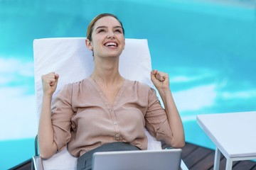 Excited woman with laptop near pool