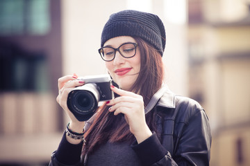 Young beautiful woman watching photo on the camera