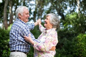 Cheerful senior couple dancing against trees