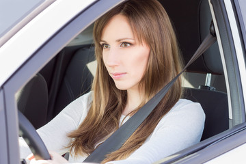 Young confident car driver woman steering wheel