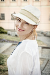 Young romantic woman posing in outdoor with sunhat