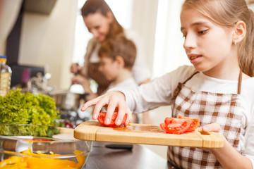 Small teenage girl cutting tomatoes in salad