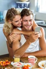 Woman embracing man using mobile phone at home