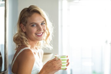Happy young woman having coffee at home