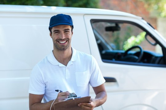 Portrait of happy delivery man with clipboard
