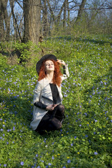 Emotional portrait of beautiful woman wearing black hat, with curly long red hair , enjoying in nature. Vivid sunny colors.