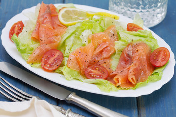 salad with smoked salmon on white dish on blue background