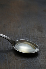 Olive oil in the spoons on wooden background. Close up