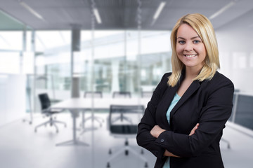 Business woman with crossed hands looking on to camera in the office