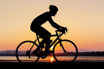 Man silhouette cycling at beach