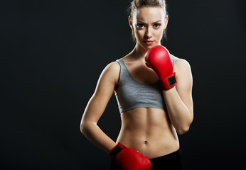 Fit, young woman boxer, black background