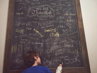 Boy writing thankful list on blackboard
