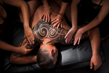 naked girl doing massage a man with a tattoo on her back