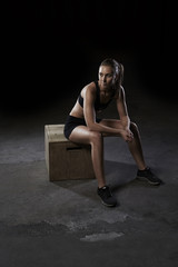 Athlete woman resting on wooden box in gym