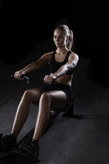 Athlete woman exercising with rowing machine in gym