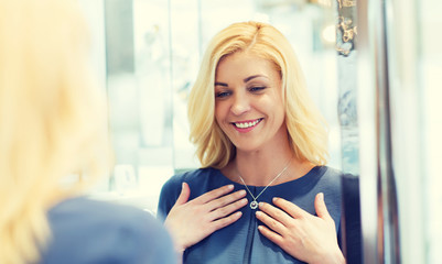 happy woman choosing pendant at jewelry store