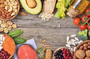 Healthy eating background. Different vegetables,nuts,oils and beeries on wooden table. Copyspace background. Top view.