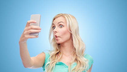 funny young woman taking selfie with smartphone