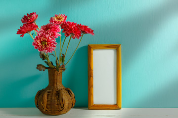 beautiful pink flower in wood vase and picture frame,on white an