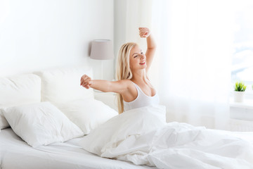 young woman stretching in bed after waking up
