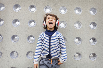 Portrait of little boy singing while listening music with headphones