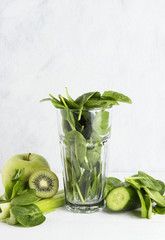 Ingredients for smoothie: spinach, kiwi, apple, celery on a whit