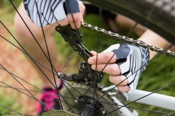 Woman fixing her bike